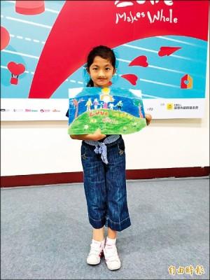 九歲的菲律賓女孩梅蘭妮拿著她的得獎作品「我的幸福快樂」。(記者林彥彤攝)