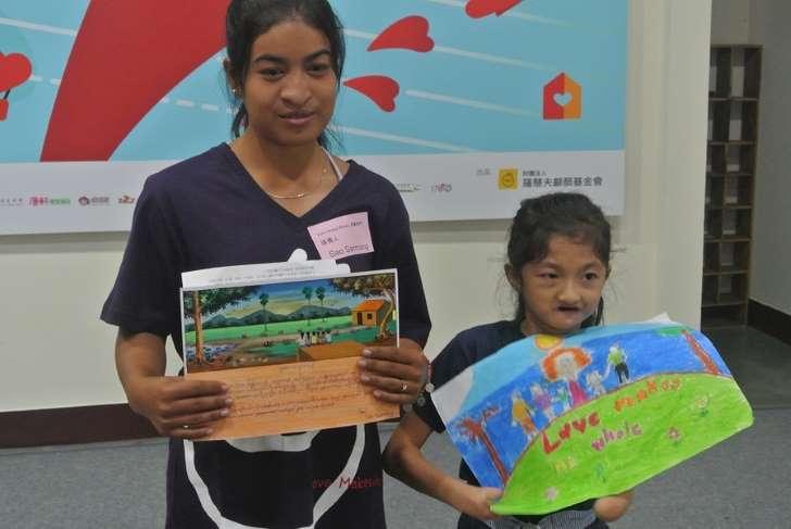 © 台灣醒報 來自柬埔寨的芍仙拿(左)與菲律賓女孩梅蘭妮(右)共同展示她們的得獎畫作《我的家園》、《我的幸福快樂
